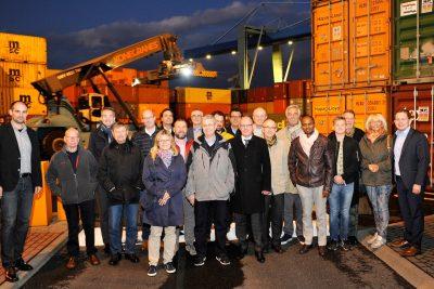 Menschen verschiedener Herkunft und Größe posieren gemeinsam vor Containern im Hafen Andernach